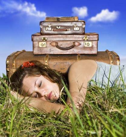 sleeping bag: Traveling young woman resting in a field with her suitcases