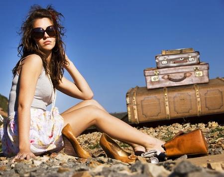 mujer con maleta: Joven viaja con sus maletas a lo largo de la carretera Foto de archivo