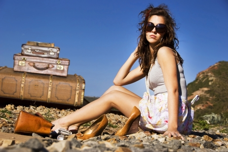 combination: Young traveling woman with her suitcases along the road
