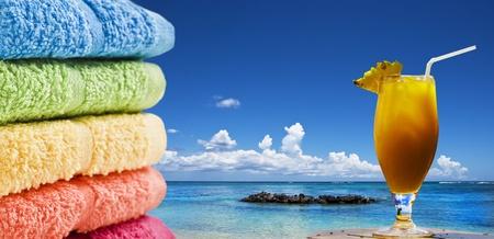 cocktail de fruits: Serviettes color�es et un cocktail de fruits sur la plage.