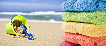 Kleurrijke handdoeken op een strand met speelgoed emmer en schep