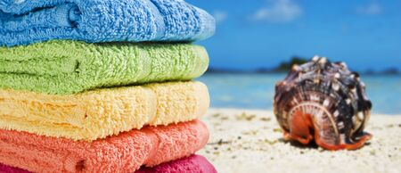 Colorful towels on a white beach with a beautiful sea shell photo