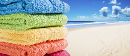 Colorful towels on a white beach on a summer day photo