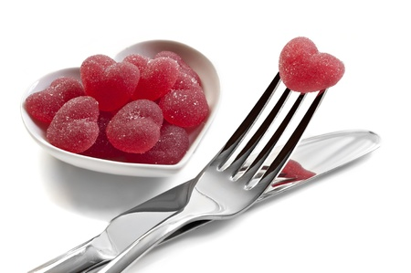 Red heart shaped jelly sweets with knife and fork on white background