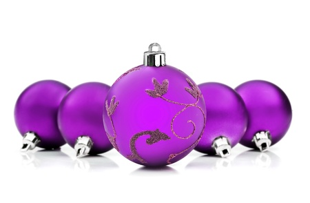 Purple christmas baubles on white background with space for text photo