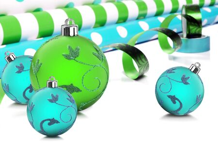 Rolls of gift wrapping paper and ribbon with blue and green christmas baubles photo