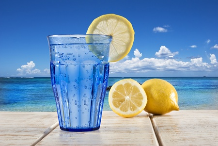 a Blue glass with sparkling water and lemon on a wooden deck overlooking a tropical beach photo