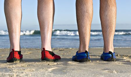 feet relaxing: The calves and feet with shoes of two men on the beach in late afternoon sunlight