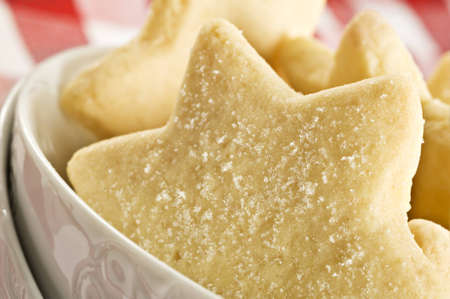 Sugar coated shortbread cookies in star shapes stacked up - on a white background with space for text photo