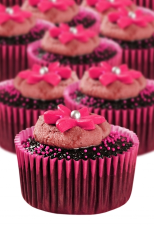 cake decorating: Delicious chocolate cupcakes in pink cups with flowers on top Stock Photo