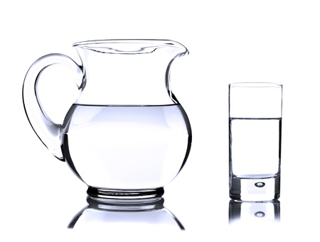 Glass jug and tumbler with water on white photo