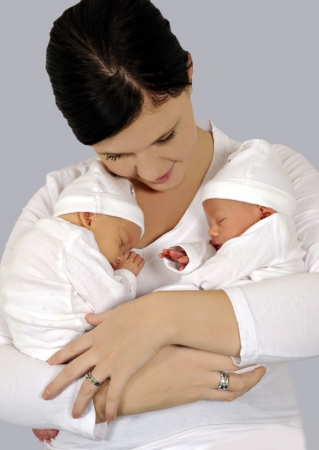 Young mother with twin babies in white clothing Stock Photo