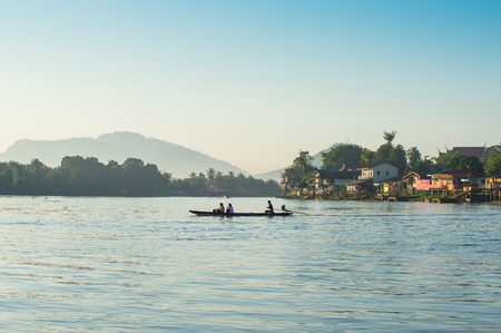 khong river: Misty morning on river with boat in Thailand
