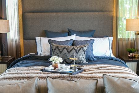 Set di tè sul letto con molti cuscini e lampada in legno in camera