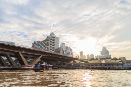 Bangkok ,Thailand - August 31, 2017 :The ferry is docking at Chao Phraya River at the morning.background is Building and bridge with morning light. Editorial