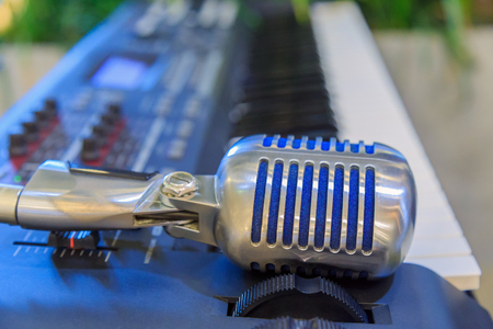A blue retro shape microphone on black electronic keyboard in the garden. Stock Photo