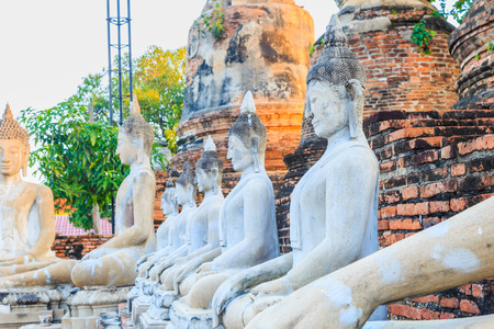 Aligned Sitting Buddha Statues with ancient ruin of temple at wat yai chaimongkol.The favorite historical attractions of Ayuttaya Thailand. Stock Photo
