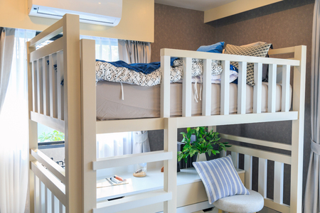 A white wooden bunk bed with a pillow and air conditioner in a childrens bedroom with warm light from a window.