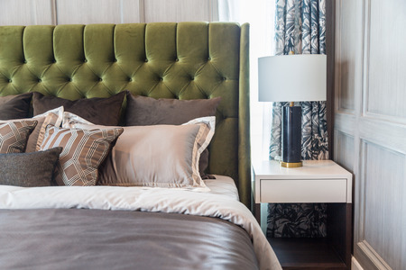 A white lamp side the bed with a brown pillows learning green headboard with a warm light from a window.