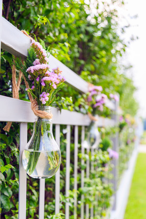 A purple flowers in light bulb shaped vase hanging on home fence with nature background.