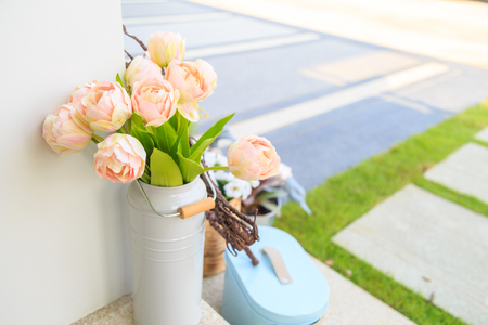 beautiful pink artificial flowers in white vase on a floor with pathway a lawn background. Stock Photo