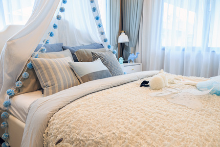 A beautiful light blue bedroom girl with a patterned pillows and angel wing and dress on the bed with modern lamp and flowers in a pot.