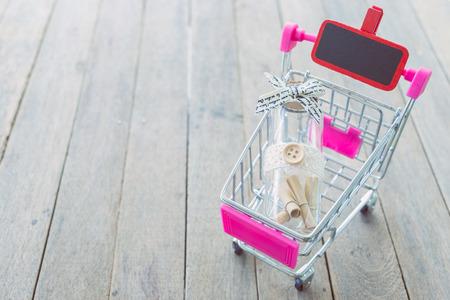 Paper rolls in a bottle in a pink mini shopping cart on wooden table. Foto de archivo