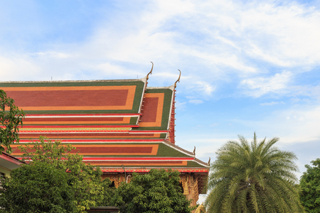 Colorful roof of Buddhist church with coconut ann mango trees against the sky and clouds.