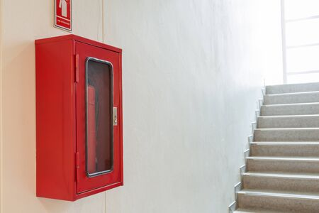 Fire extinguisher cabinet on white wall near staircase for building security.