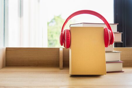 A brown book  wearing red headphone learning book pile on wooden table next the window and blinds, blank for copy space.