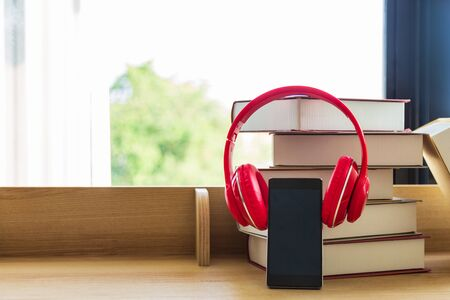 A black mobile phone  wearing red headphone learning book pile on wooden table next the window and blinds, blank for copy space. Stockfoto