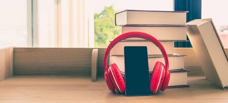 A black mobile phone  wearing red headphone learning book pile on wooden table next the window and blinds, blank for copy space with pastel color. Stockfoto