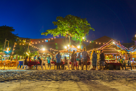 Rayong, Thailand - October 14, 2018 : Tourist family choosing restaurants for dinner on the Samet island at night, Samet islands favourite tourist attractions in Thailand. Editorial