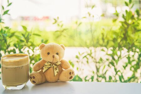 A cute brown teddy bear sitting on white table side a cup of coffee next a glass window seeing nature outside background with filter color.