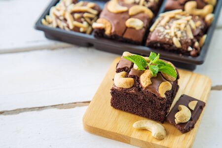 Chocolate brownies with cashew nut and papermint on wooden plate on white wooden floor with brownies box blurred background.