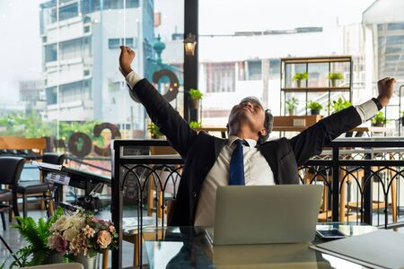 Close up middle aged business Asian man in formal suit sitting in front of laptop and stretching his arms after worked for a long time at modern office with and old low building background.
