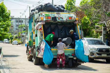 Nonthaburi, Thailand- May 15, 2020 : Local garbage collector is collecting garbage into the garbage truck in home village in the morning.