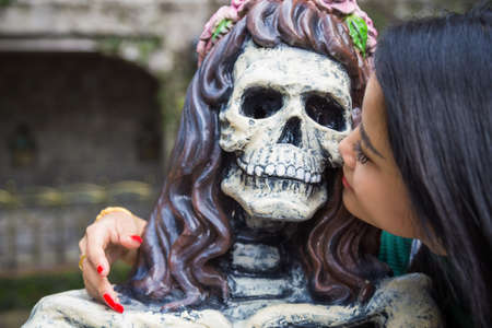 Close up a skeleton woman statue with an Asian woman kissing. Фото со стока