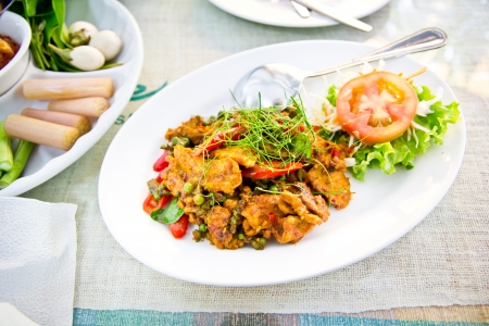 Dried pork with spicy curry on white plate in restaurant  Stock Photo