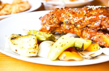 grilled pork ribs steak on white plate photo