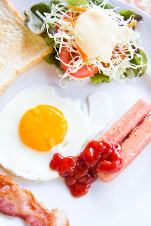fried eggs with bacon, sausages and toasts on white plate Stock Photo