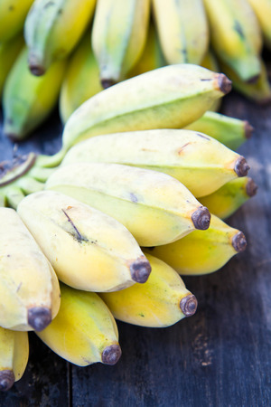 Cultivated bananas on wooden table photo