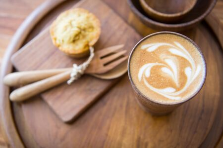 romantics: Latte art coffee on wooden cup with pumpkin muffin Stock Photo