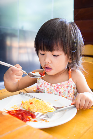 wooden chair: A Little asian girl eating omlet and siting on wooden chair in the restaurant