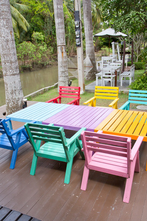 armchairs: Colorful wooden armchairs beside a river