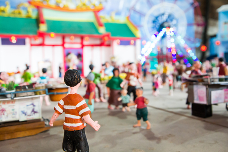 a wonderful world: Lighting on the ferris wheel and temple at night with traditional craft dolls Stock Photo