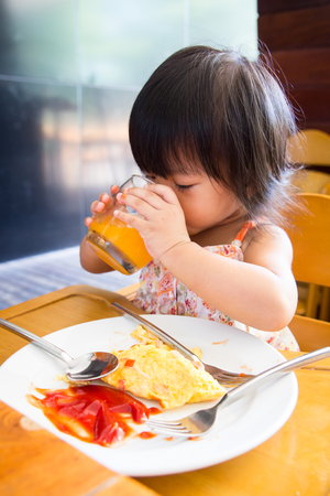 omlet: A Little asian girl eating omlet and siting on wooden chair in the restaurant
