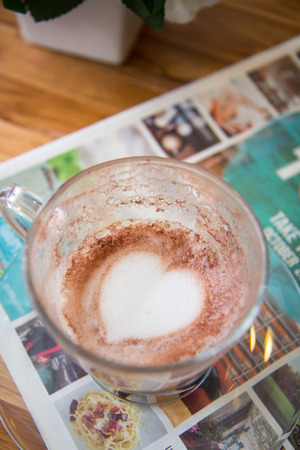 cappucino: Finish a cup of cappucino with heart shape on bubble milk