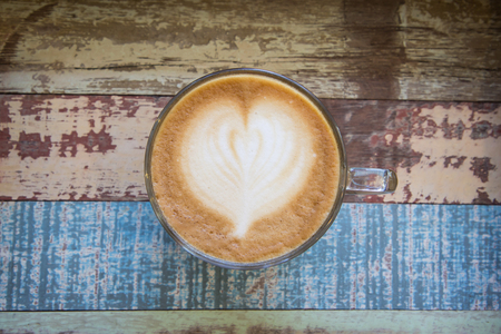 capacino: Heart latte art coffee on vintage wooden background Stock Photo
