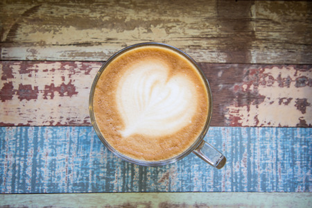 Heart latte art coffee on vintage wooden background Stock Photo